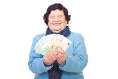 Más vieja mujer feliz que sostiene billetes de banco euro Fotografía de archivo