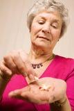 Más vieja señora mayor que toma una tablilla o una píldora Imagen de archivo libre de regalías