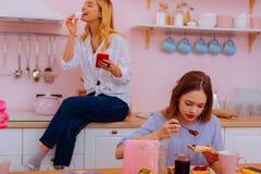 Más viejas y más jovenes hermanas que comen el desayuno delicioso junto imagen de archivo libre de regalías