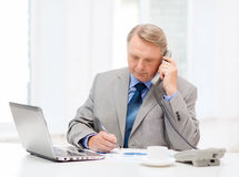 Más viejo hombre de negocios ocupado con el ordenador portátil y el teléfono Foto de archivo libre de regalías