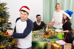 Más viejos padres con los niños adultos que se preparan para la Navidad en hogar Foto de archivo libre de regalías