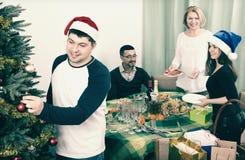 Más viejos padres con los niños adultos que se preparan para la Navidad en hogar Fotos de archivo libres de regalías