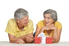 Más viejos pares felices con el regalo imagenes de archivo