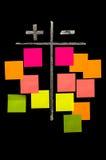Más y menos en la pizarra con las notas pegajosas del color Foto de archivo