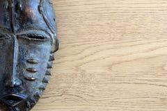 Máscara africana del hierro en fondo de madera fotografía de archivo