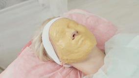 Máscara amarilla en cara del ` s de la mujer almacen de metraje de vídeo