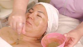 Máscara antienvejecedora de la prueba cosmética de algas El cosmetólogo profesional mezcla los ingredientes en una taza rosada Sa almacen de metraje de vídeo