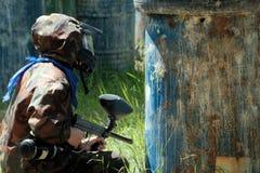 Máscara, armas, camuflagem e um lenço azul do jogador durante o jogo do paintball Esperando o inimigo na emboscada seja foto de stock