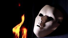 Máscara blanca de la mística cerca del fuego