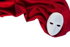 Máscara blanca en tela de seda roja Foto de archivo libre de regalías