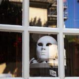 Máscara branca atrás de uma janela em Aix en Provence França 23 de maio de 2015 Aix en Provence França Fotografia de Stock Royalty Free