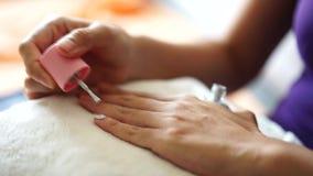 Máscara cosmética em mulheres do tratamento da cara A mão da mulher é pintada no prego video estoque
