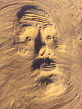 Máscara da escultura da areia em uma praia Foto de Stock