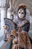 Máscara da mulher que guarda o fã e que veste o traje ornamentado do ouro e o preto sob os arcos no palácio dos doges durante o c Fotografia de Stock Royalty Free