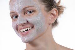 A máscara de dois cosméticos da argila cinzenta com esfrega e desnata na cara Fotos de Stock Royalty Free