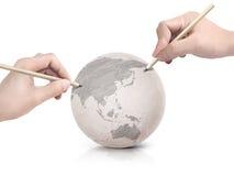 Máscara de duas mãos que tira o mapa de Ásia na bola de papel Foto de Stock