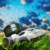 Máscara de gás que encontra-se na grama contra o céu fumarento Fotografia de Stock