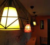 Máscara de lâmpada dourada em um café foto de stock