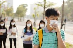 Máscara de la boca del estudiante que lleva contra niebla con humo en ciudad imagen de archivo