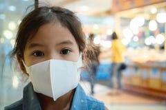Máscara de la protección de la muchacha asiática linda del niño que lleva contra a la contaminación de la niebla con humo del air foto de archivo