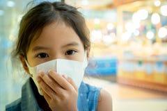 Máscara de la protección de la muchacha asiática linda del niño que lleva contra a la contaminación de la niebla con humo del air foto de archivo libre de regalías