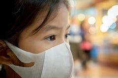 Máscara de la protección de la muchacha asiática linda del niño que lleva contra a la contaminación de la niebla con humo del air imagen de archivo