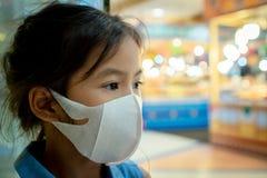 Máscara de la protección de la muchacha asiática linda del niño que lleva contra a la contaminación de la niebla con humo del air fotos de archivo