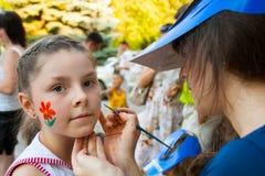 Máscara de las pinturas del artista en la cara de una muchacha en un día de fiesta de los niños en el parque en Stalingrad Foto de archivo