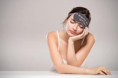 Máscara de olho vestindo da mulher do sono fotos de stock royalty free