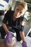 Máscara de oxígeno de la explotación agrícola del paramédico sobre la cara del paciente foto de archivo libre de regalías