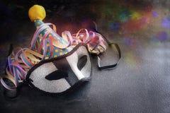 Máscara del carnaval con un sombrero divertido y y la serpentina colorida del partido Imagen de archivo