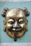 Máscara del chino del latón/del bronce en la pared verde del cemento Fotografía de archivo