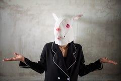 máscara del conejo que muestra la muestra curiosa de la mano Imagen de archivo