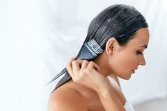 Máscara del pelo Mujer que aplica el acondicionador en el pelo largo con el cepillo, tratamiento del cuidado del cabello imagen de archivo