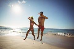 Máscara del salto de los pares que lleva que salta en la playa Fotos de archivo