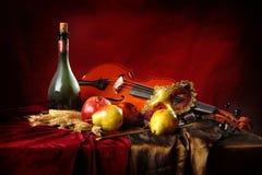 Máscara del violín y de la mascarada en un fondo rojo al lado de una botella de vino y de fruta viejos Fotos de archivo libres de regalías