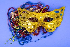 Máscara do carnaval do ouro com os grânulos coloridos no fundo violeta Imagem de Stock