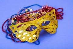 Máscara do carnaval do ouro com os grânulos coloridos no fundo violeta Imagens de Stock