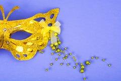 Máscara do carnaval do ouro com os grânulos coloridos no fundo violeta Fotografia de Stock