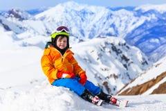 Máscara e capacete vestindo de assento de esqui do menino no inverno Foto de Stock