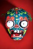 Máscara esquelética coloreada en un fondo rojo Foto de archivo libre de regalías