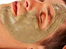 Máscara facial da lama do homem no salão de beleza dos termas Massagem de cara foto de stock