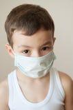 Máscara médica de la gripe del niño del muchacho del niño epidémico de la medicina Foto de archivo libre de regalías