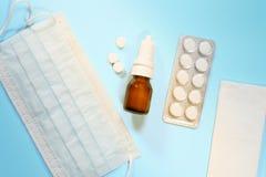 Máscara médica, pañuelos, espray nasal y medicación en un fondo azul claro Concepto de tratamiento del frío, gripe fotos de archivo libres de regalías