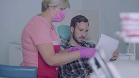 Máscara médica y guantes del dentista i femenino que muestran a la imagen paciente masculina de sus dientes El hombre joven que v almacen de metraje de vídeo