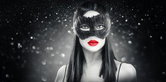 Máscara oscura de la pluma del carnaval de la mujer morena del encanto de la belleza que lleva, partido sobre fondo del negro del foto de archivo