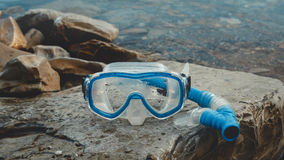 Máscara para Freediver e mentira do tubo de respiração na praia, nas rochas Conceito do turismo e do curso fotografia de stock