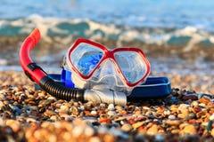 Máscara para mergulhar e um tubo de respiração em um close-up de Pebble Beach contra o mar imagem de stock