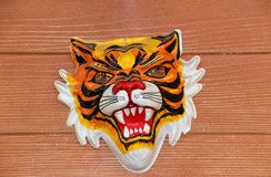 Máscara plástica do tigre real que pendura na parede marrom do cimento da fibra fotografia de stock