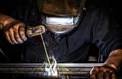 A máscara profissional protegeu o homem do soldador que trabalha na soldadura do metal e acende o metal foto de stock royalty free